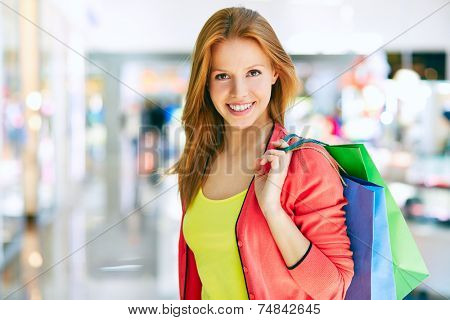 Charming customer with shopping bags looking at camera
