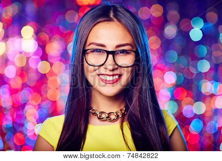 Asian female in eyeglasses looking at camera at party