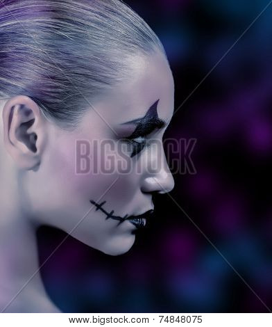 Side view of zombie girl with creepy makeup on blue and purple blurry background, night of horror, time for witches and vampire, Halloween holiday concept
