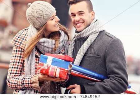 A picture of cheerful young people doing Christmas shopping