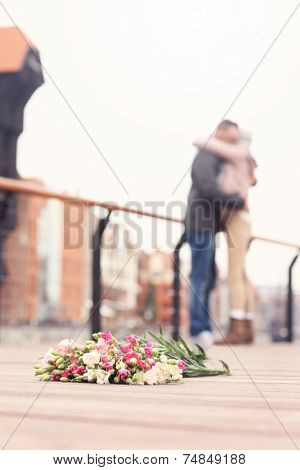 A picture of flowers and hugging couple in the background