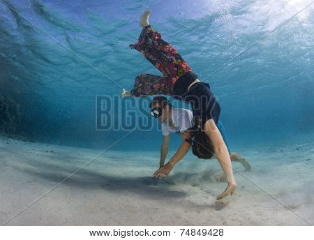 Young couple dancing and improvising underwater