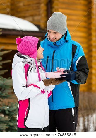Half-length portrait of man giving present to female outdoors during winter vacations