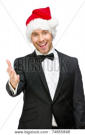 Half-length portrait of businessman wearing Santa Claus cap who handshake gestures, isolated on white. Concept of holidays and Christmas