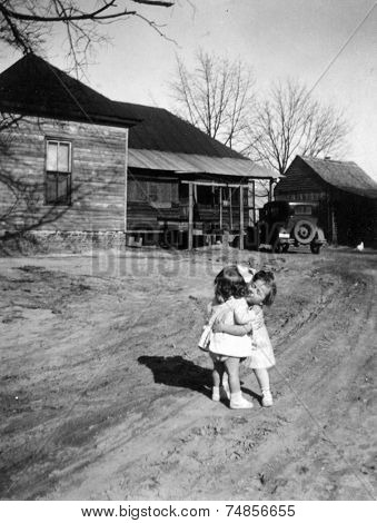 CANADA - CIRCA 1960s: Vintage photo shows two little girls hugging on the street.