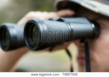 hunting, war, army and people concept - close up of young soldier, ranger or hunter with binocular observing forest