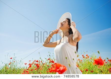 happiness, nature, summer, vacation and people concept - smiling young woman with closed eyes wearing straw hat on poppy field