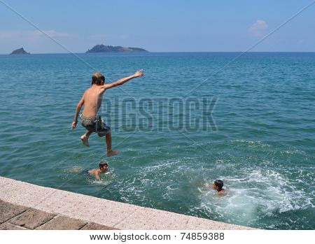 Boys jumping into sea off of the jetty on Petra seafront