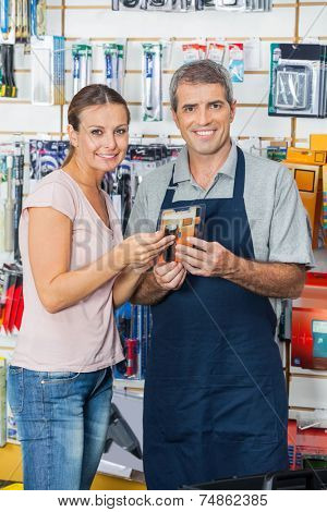 Portrait of smiling female customer and salesman holding flashlight in hardware store