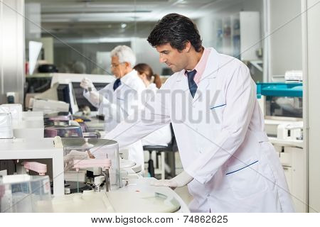 Mid adult male technician experimenting in laboratory using centrifuge