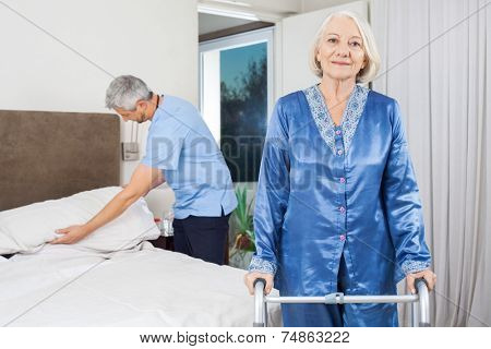 Portrait of senior woman standing with walking frame while caretaker making her bed at nursing home