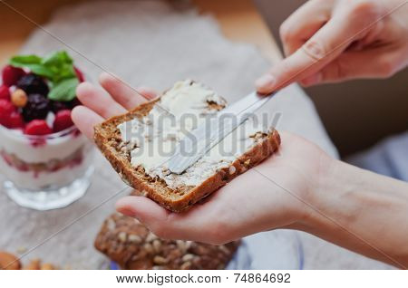 Woman Hand  Rubs Butter On Piece Of Rye Bread