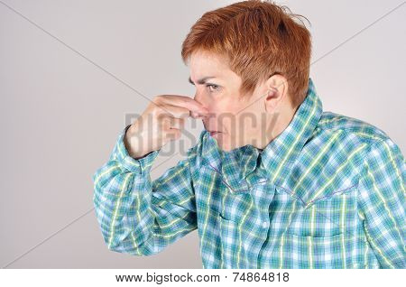 Woman holding her nose with her fingers