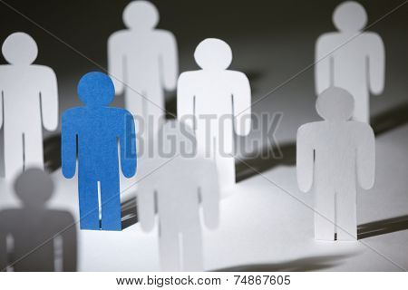 Close up of group of standing paper people. Lots of similar copies of a paper man, but a blue one stands out among them. Concept of teamwork and leadership