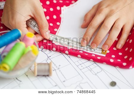 A Tailor Is Laying Out A Dress/sewing Layout