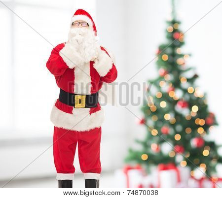 holidays and people concept - man in costume of santa claus with bag making hush gesture over living room and christmas tree background