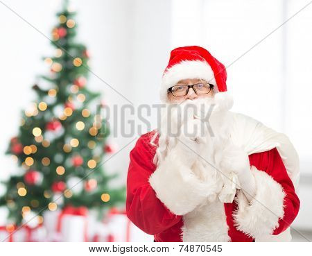 christmas, holidays and people concept - man in costume of santa claus with bag making hush gesture over living room with tree