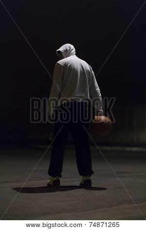 Portrait of a hooded basketball player holding the ball in one hand