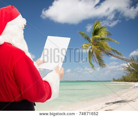 christmas, holidays, travel and people concept - man in costume of santa claus reading letter over tropical beach background