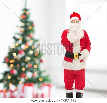 holidays and people concept - man in costume of santa claus making hush gesture over snowy city background over living room and christmas tree background