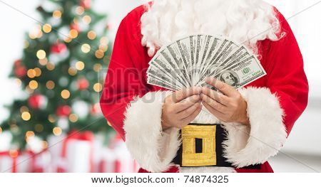 christmas, holidays, winning, currency and people concept - close up of santa claus with dollar money over living room with tree