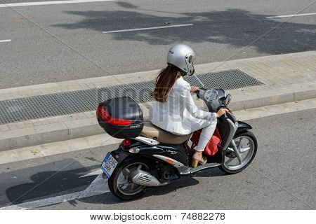 Young Woman Is Driving Scooter In Barcelona Street, Catalonia, Spain.