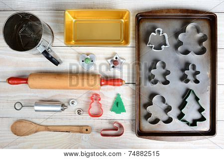 High angle shot of Christmas Cookie baking tools. Horizontal format on a white rustic kitchen table. Items include: rolling pin, cookie cutters, press, spoon, pans, and sifter.