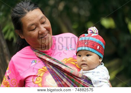 BAAN LOOK KAO LAM, THAILAND, NOVEMBER 20, 2012 : Unidentified mother from a Lahu tribe is proudly presenting his baby in the village of Ban look Kao Lam, north Thailand.