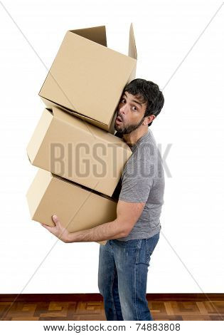 Young Man Moving In A New House Carrying Pile Of Cardboard Boxes