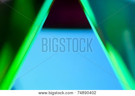 Close-up of optical glass prism and light reflection. blue and green reflection of a glass prism.