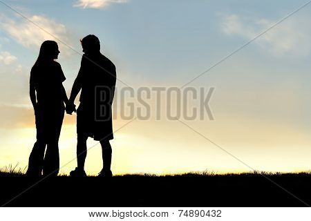 Silhouette Of Happy Couple Holding Hands And Talking At Sunset