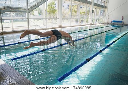 Side view of a fit swimmer diving into the pool at leisure center