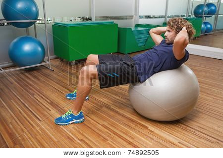 Side view of handsome young man doing abdominal crunches on fitness ball in gym