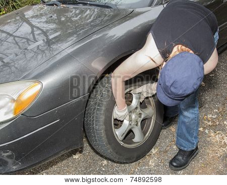Young women changing tire on side of the road