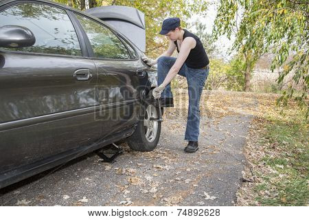 Young women changing a tire on the street