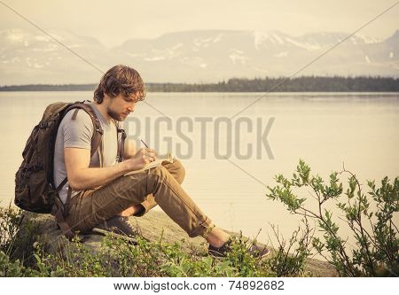 Young Man Traveler with backpack reading book and writing notes outdoor