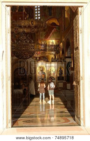 PODGORICA, MONTENEGRO - AUGUST, 17: a couple inside the Cathedral of the Resurrection in Podgorica looking at Jesus Christ icons. Shot in 2014