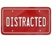 stock photo of attention  - Distracted word on a red license plate to illustrate a dangerous driver who is texting or doing something diverting attention from driving on the road - JPG