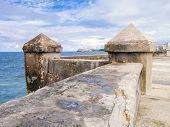 stock photo of el morro castle  - The famous Malecon seawall in Havana with El Morro castle on the background - JPG