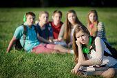 foto of peer-pressure  - Lonely female teen student sitting near group - JPG