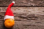 stock photo of mandarin orange  - mandarin orange in a Christmas hat on orange background - JPG