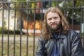 pic of long beard  - Blond long hair and beard young adult hipster man listening music. Outdoor, urban scene. ** Note: Shallow depth of field - JPG
