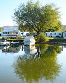 stock photo of caravan  - Campsite on a lake with caravans and boats - JPG