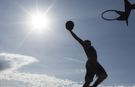 stock photo of slam  - A silhouette of a male basketball player on an outdoor court slam dunking - JPG