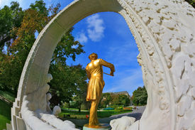 stock photo of waltzing  - Elegant bronze statue with violin shines in the bright summer sun - JPG