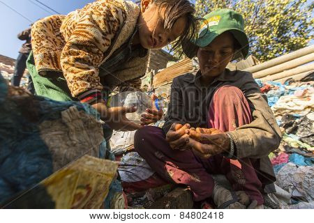 KATHMANDU, NEPAL - CIRCA DEC, 2013: Unidentified child and his parents during lunch in break between working on dump. Only 35% of population Nepal have access to adequate sanitation.