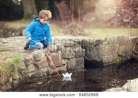 Child playing with paper boat and stick on bridge by water