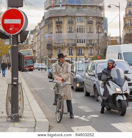 Cyclists and motorcyclists on a busy intersection in Paris waiting for the green light, France