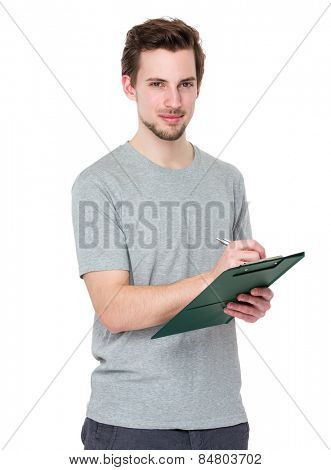 Young man write on clipboard
