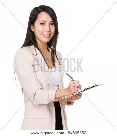 Asian businesswoman write on folder